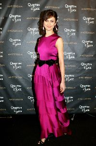 Olga Kurylenko : Olga picture on the red carpet wearing a dark pink dress with a black waist ribbon at the Quantum of Solace in Amsterdam movie Premiere
