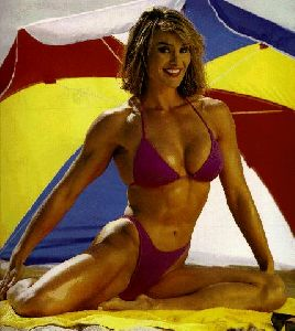 Cory Everson : Corey Everson wearing a pink bikini under a beach umbrella