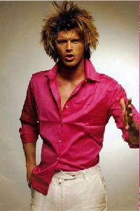 Kivanc Tatlitug : as a model at a fashion show wearing a pink shirt with large hair