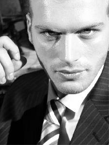 Kivanc Tatlitug : black and white face closeup wearing a suit and a neck tie