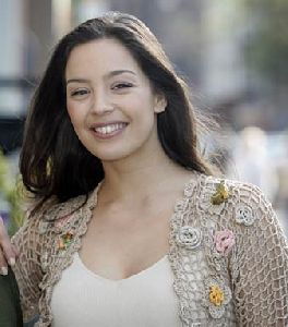 Azra Akin : smiling on the street to the camera wearing a beige knit jacket