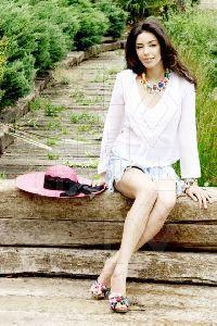 Azra Akin sitting on a tree bench