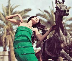 Azra Akin portrait wearing a green dress standing beside a stone engraved horse