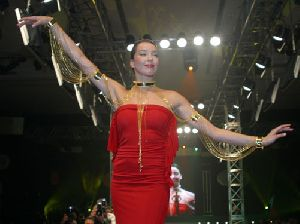 Azra Akin at a fashion show in a red stunning cocktail dress