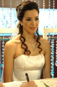 Azra Akin as a bride in full makeup and a wedding dress