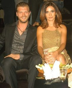 Songul Oden wearing a golden dress accompanied with Kivanc Tatlitug